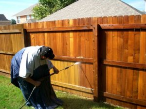 man power washing a fence to prep for stain